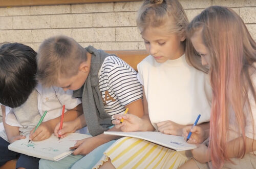 4 children sitting on bench outside school writing in notebooks