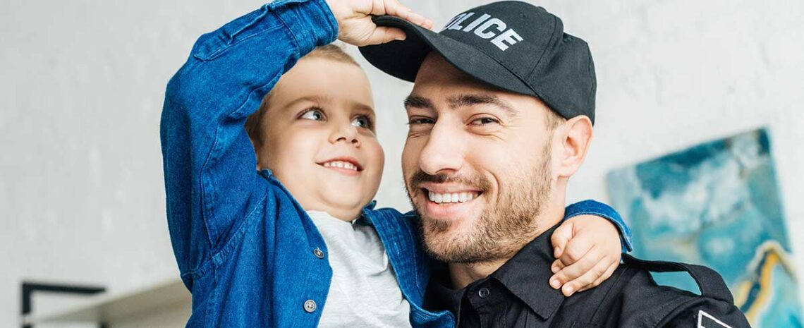 Police officer smiling at camera while young boy plays with his hat